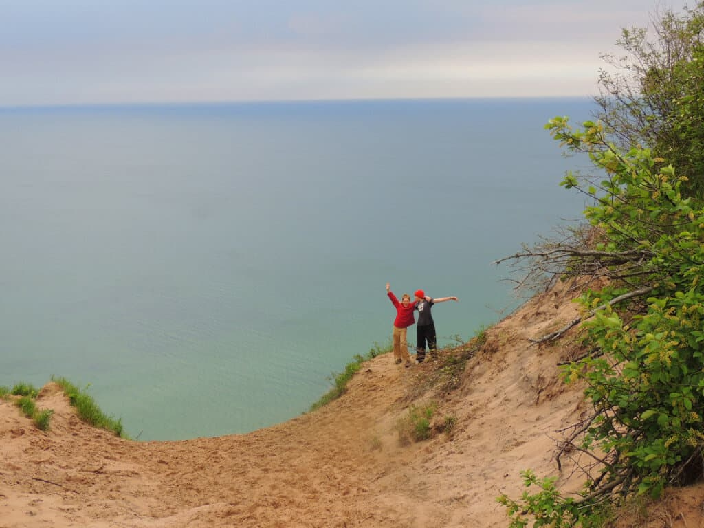 two boys stand on the edge of a sand dune on the shores of Lake Superior during a family lake vacation.