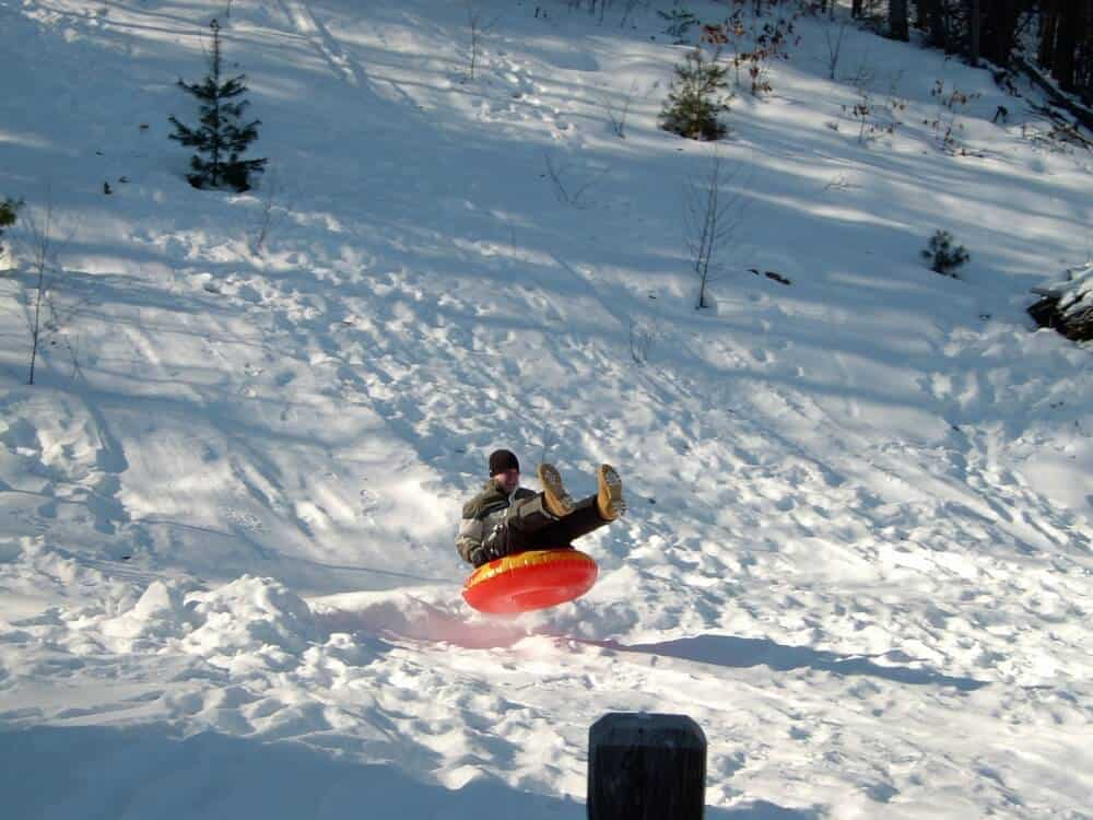 A man slides down a snowy hill on a snow tube.