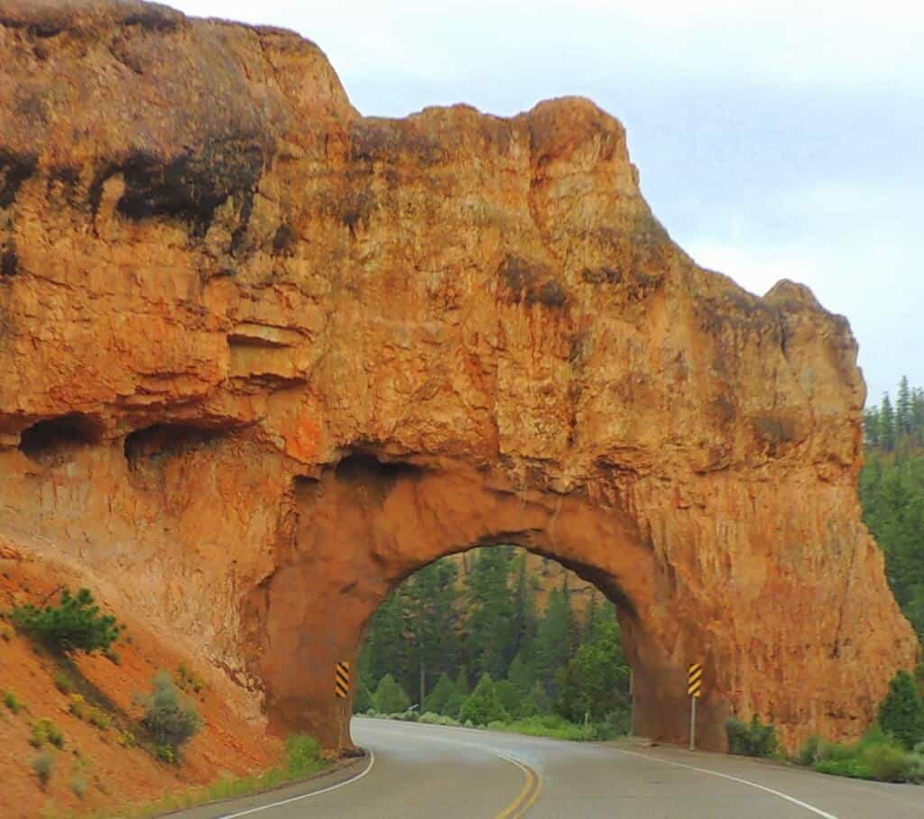 A red rock tunnel straddles highway 12 in Red Canyon, Utah