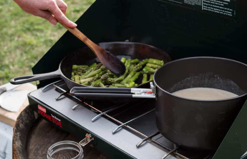 A two-burner camp stove and a pan with asparagus and a pot of soup.