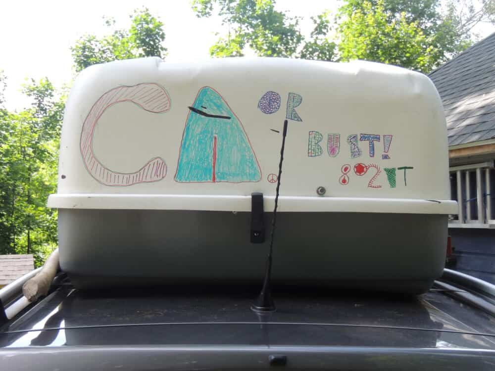 "A cargo box with ""CA or Bust"" written on it with markers."