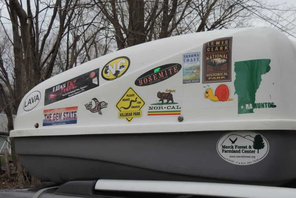 A photo of a white and grey cargo box with stickers all over it.