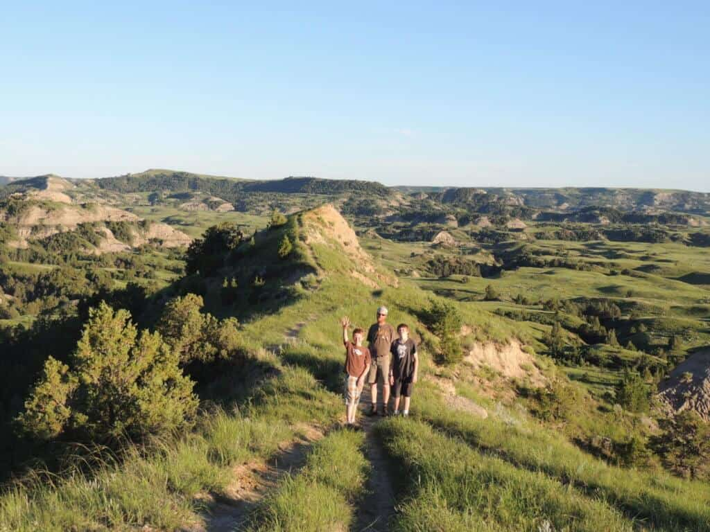 A man and two children stand on a hiking trail in Theodore Roosevelt National Park.
