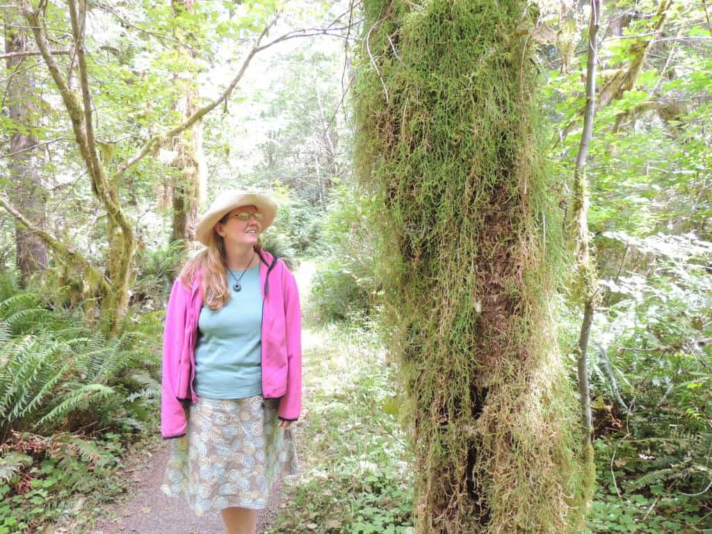 A woman hikes along the Kestner Homestead Trail in the Quinault Rainforest in Olympic National Park.