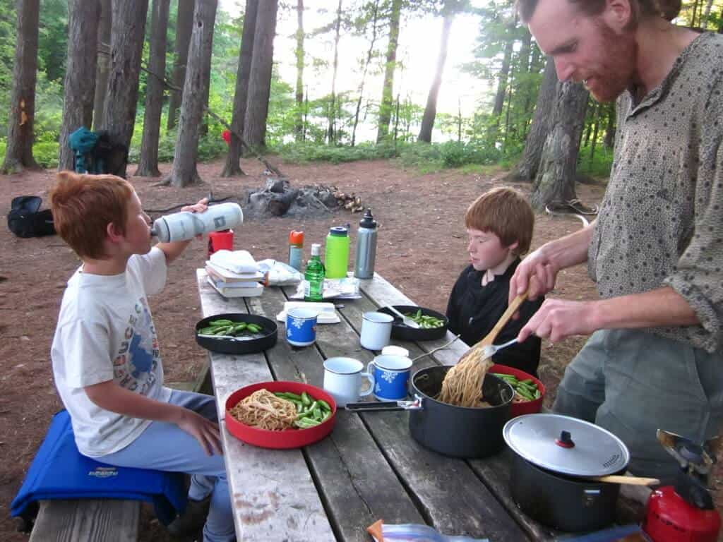 A family enjoys a car camping dinner in the forest.