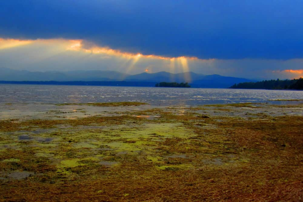 Sun setting through the clouds over the Adirondacks and Lake Champlain in Vermont