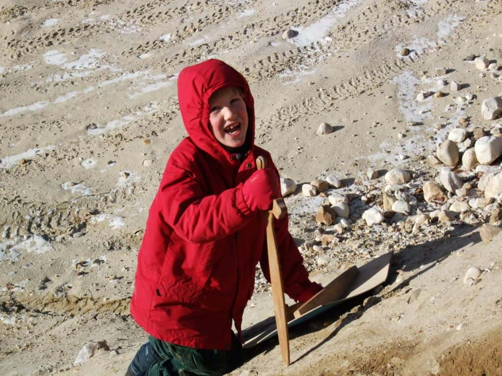 A young boy plays in the dirt wearing a bright red winter jacket.
