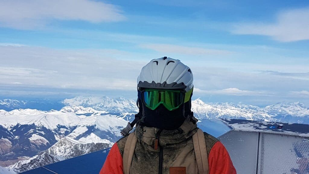 A person all decked out in ski gear stands at the top of a mountain with snow-capped peaks in the background.
