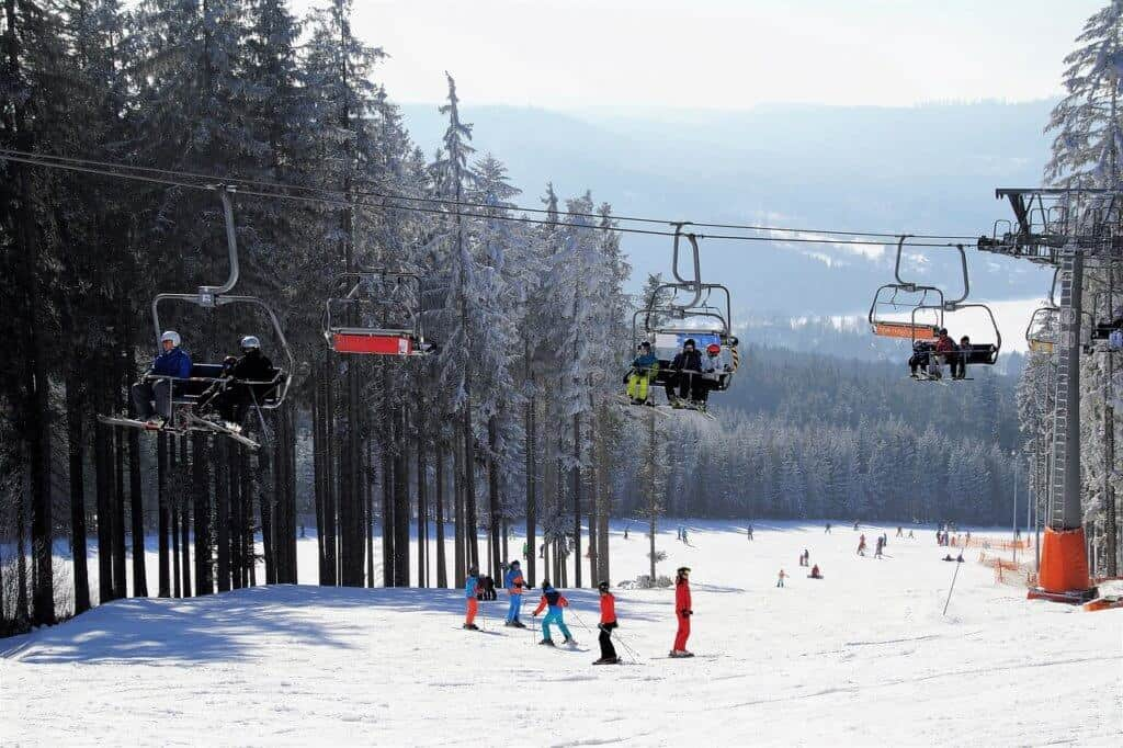 A ski lift with people sitting on the chairs. Underneath there are a lot of skiers wearing colorful ski jackets.