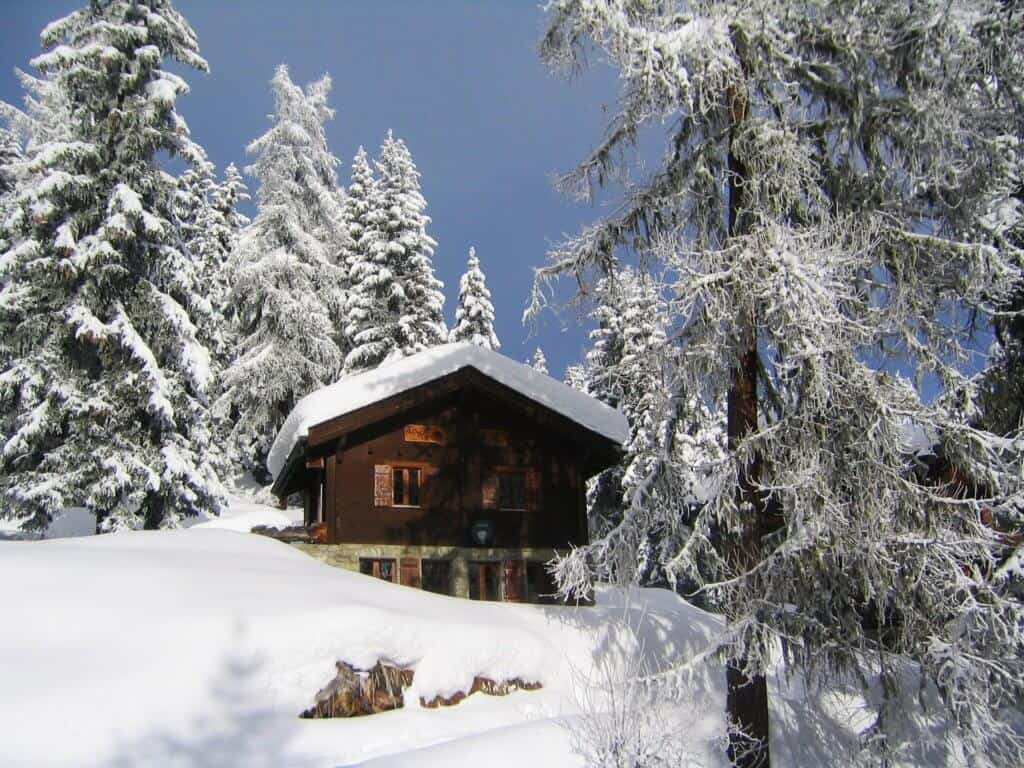 A ski chalet in the mountains, covered with snow.