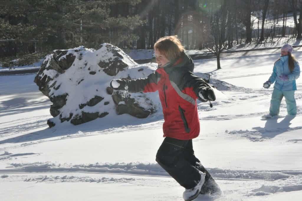 Two children throw snowballs in a field.
