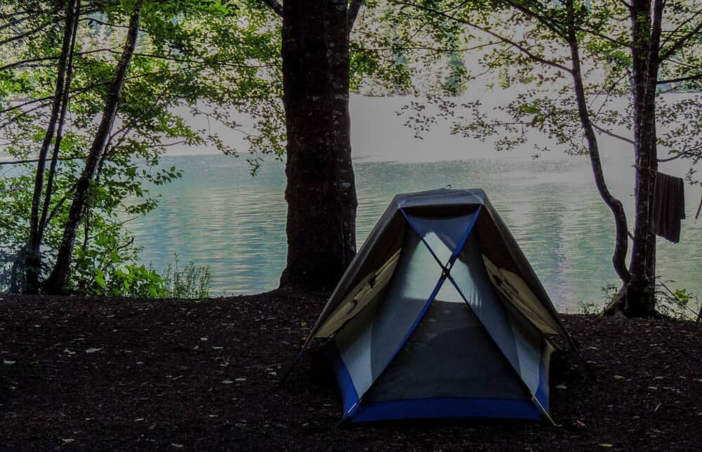 a small tent on the edge of a bright blue lake in North Cascades National Park