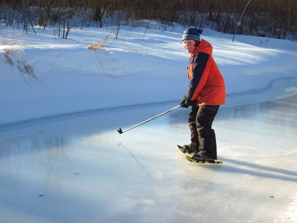 A boy stands in snowshoes on an icy stream. He is using a pole as a baseball bat.