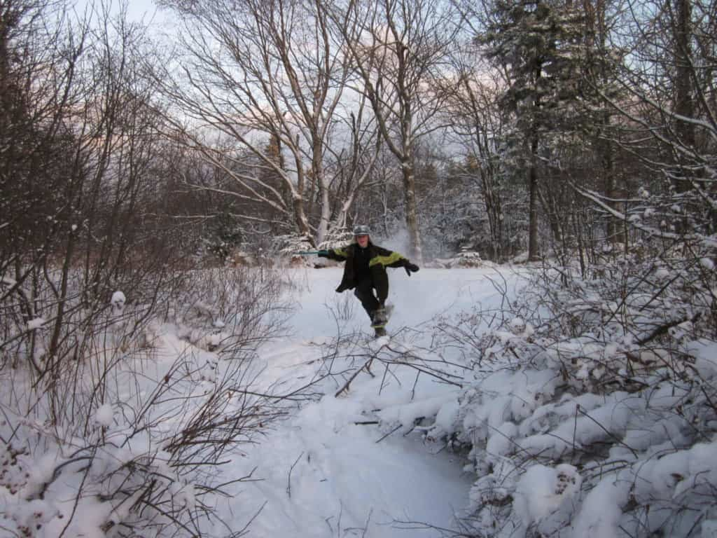 A boy runs through the woods on snowshoes.