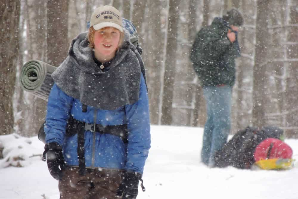 A boy hikes through the snow to get to his camping cabin in New England