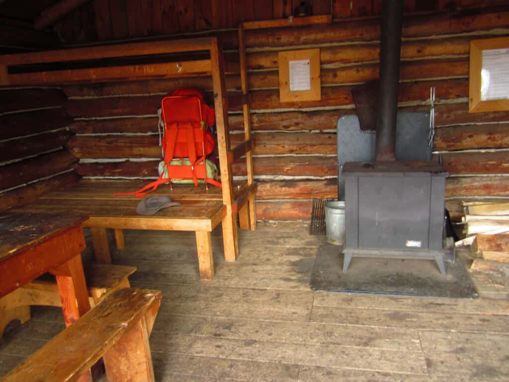 The inside of a camping cabin at Merck Forest. Picture shows a woodstove, some wooden bunks, and an orange backpack.