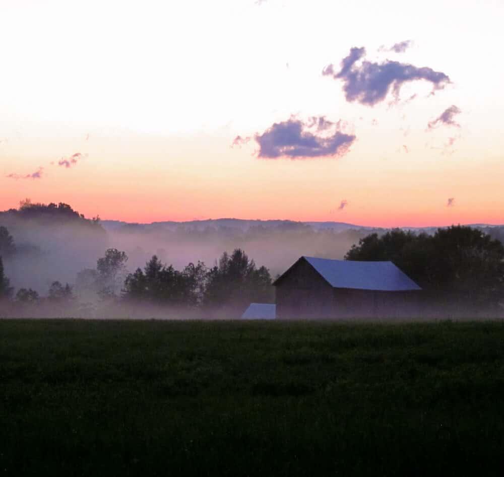 A foggy sun sets over a barn in Bennington VT