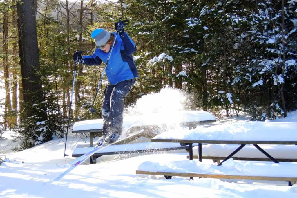 A skiier jumping of a picnic table covered with snow in Woodford State Park