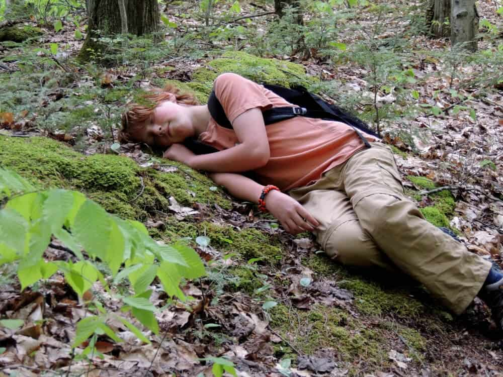 A young boy naps in the forest during a hiking trip. He is wearing a backpack and an orange shirt.