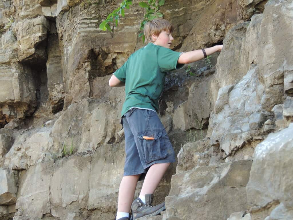Rowan hunts for Herkimer diamonds on the side of a cliff.