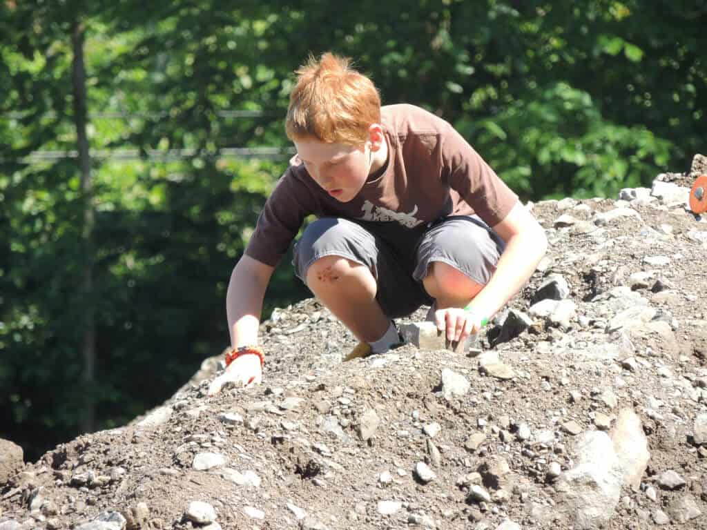 A boy sorts through rubble in search of Herkimer diamonds