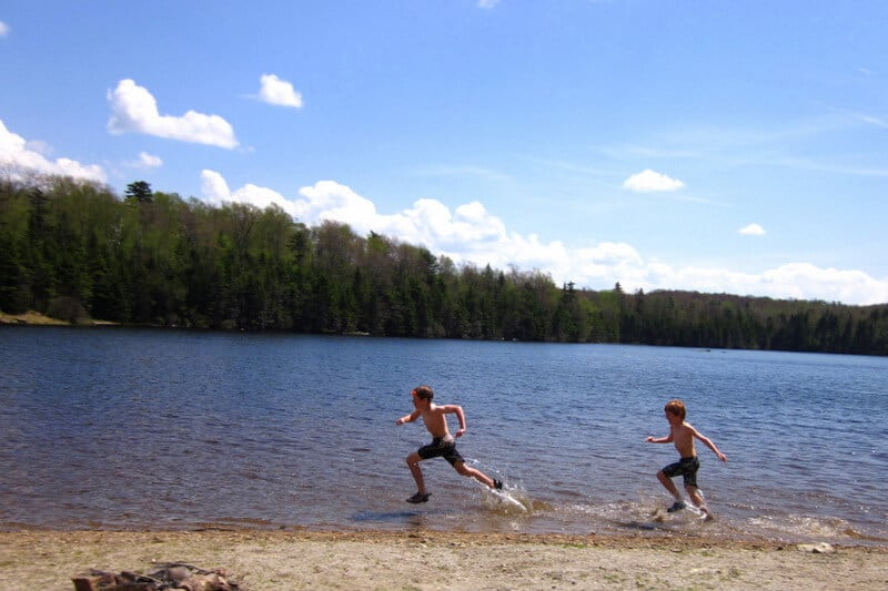 Two boys running through the water near the beach at Woodford State Park