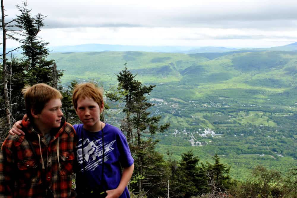 Two kids sit in front of a mountain vista in Vermont on a cloudy day.