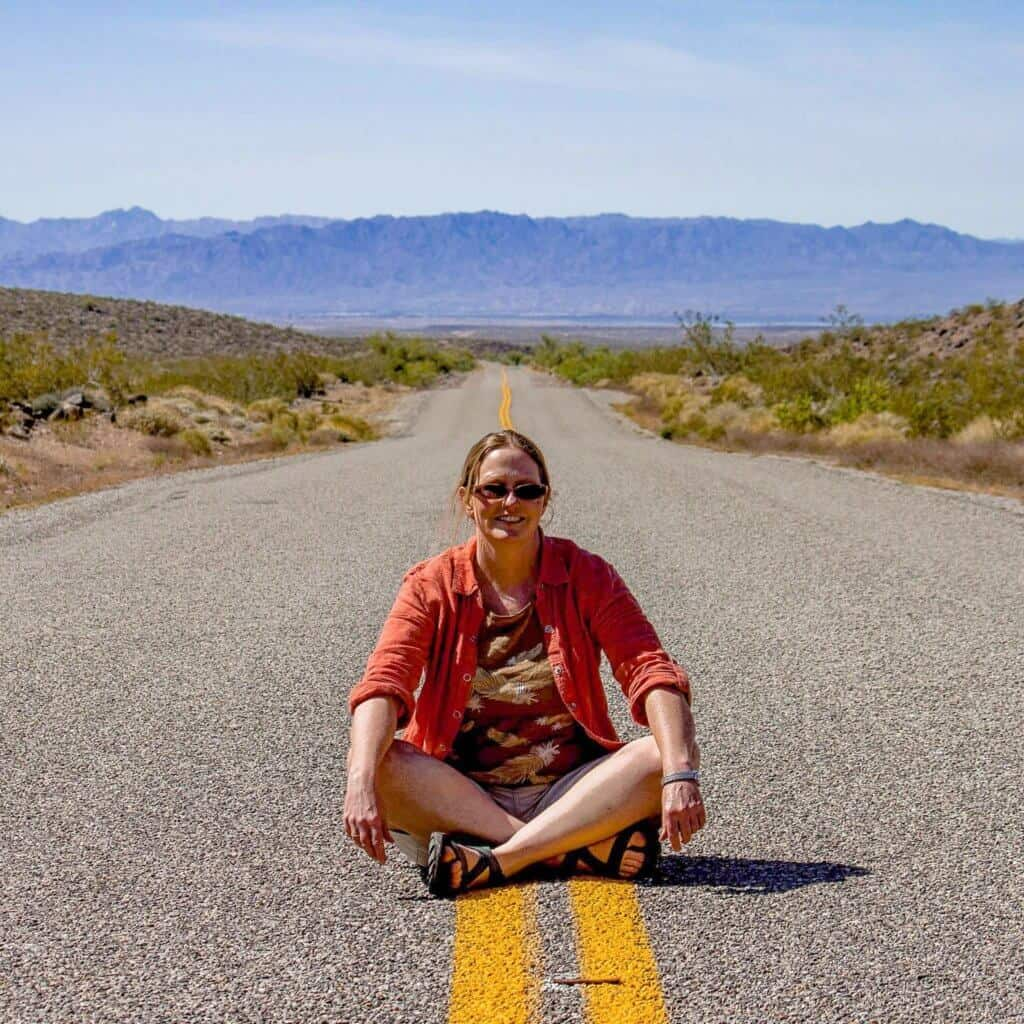 A woman sits in the middle of the road on Route 66 in Arizona.