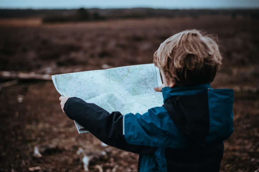 A young boy stands in a field looking at a map.