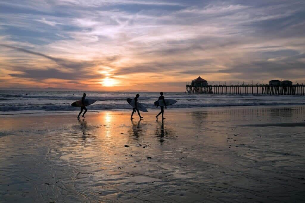 A group of three surfers walk along the shore during sunset at Huntington Beach, CA.