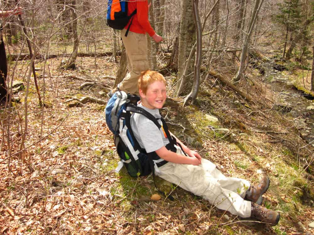 Gabriel sits on the ground wearing a backpack during a hike around Woodford State Park in Vermont.