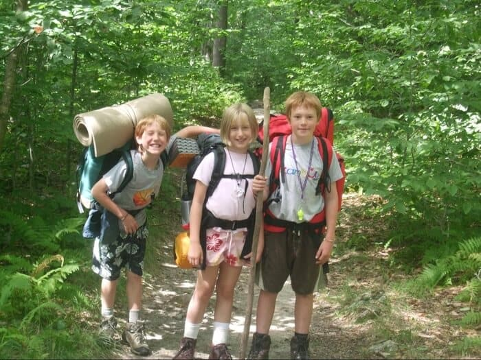 Three kids wearing backpacking packs standing on a trail after a long hike.