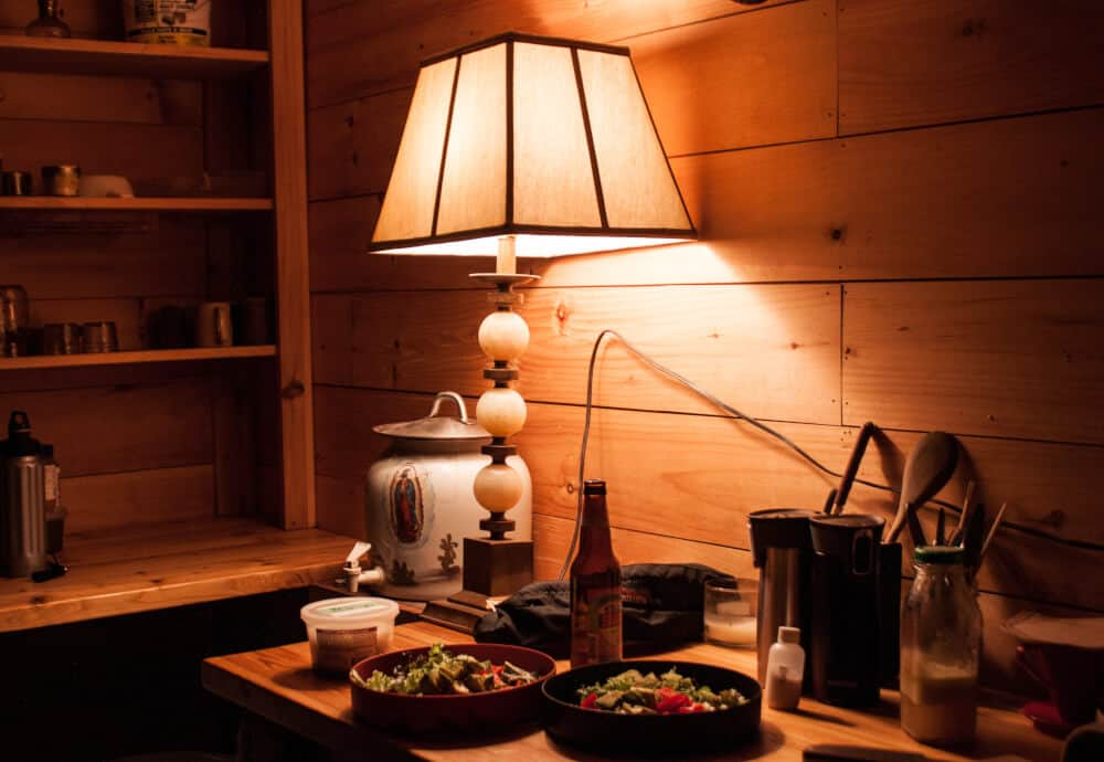 A corner of the Vermont cabin rental at Stony Pond Farm. The kitchen counter with a lamp, and two plates with food on them.
