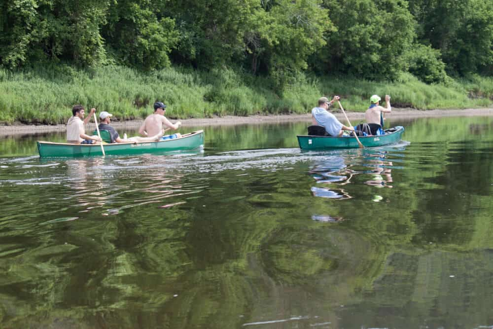 Two canoes paddled by several young men on the Connecticut River