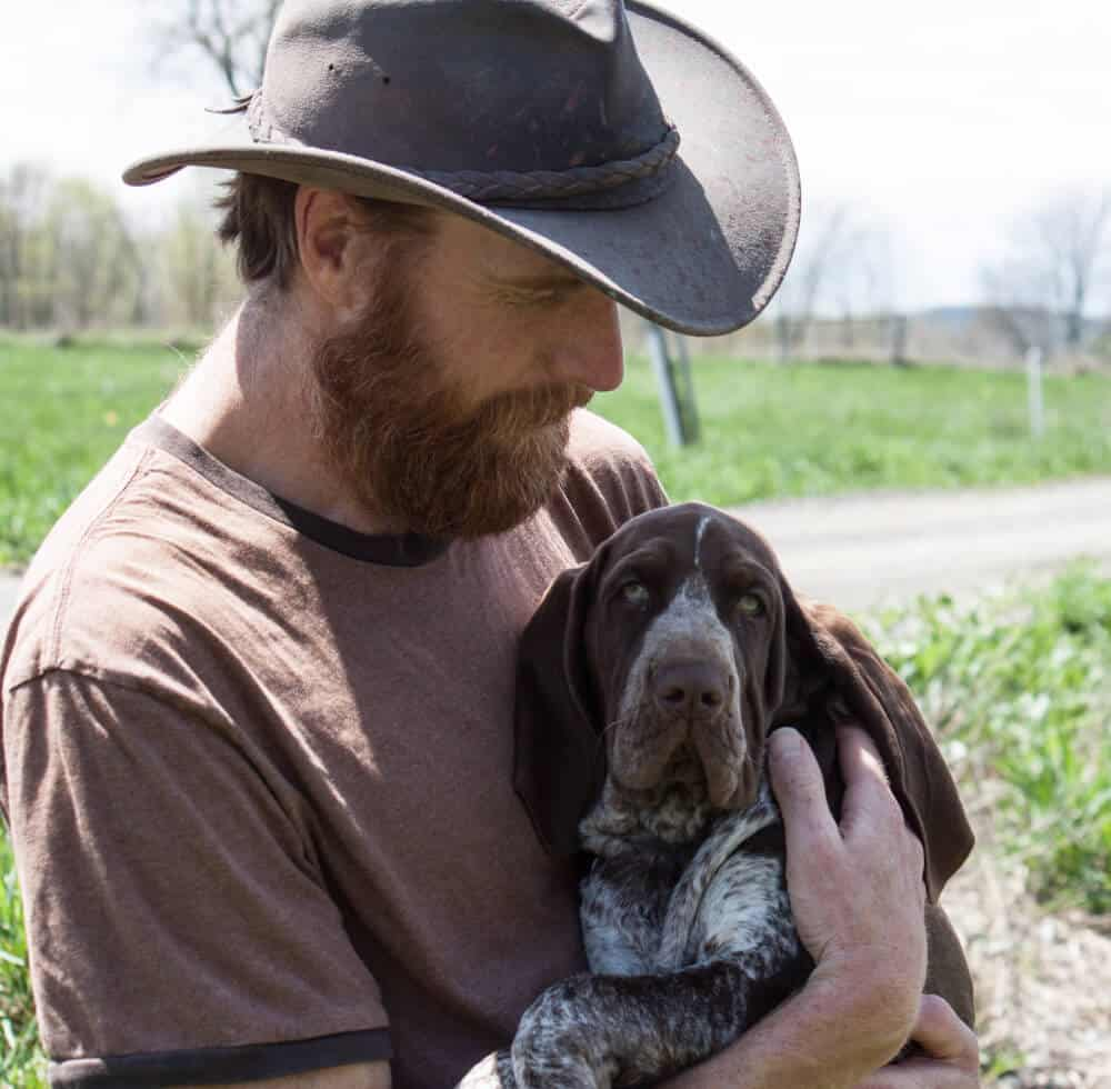 Eric, wearing a leather cowboy hat, and holding a hound-dog puppy. Vermont.
