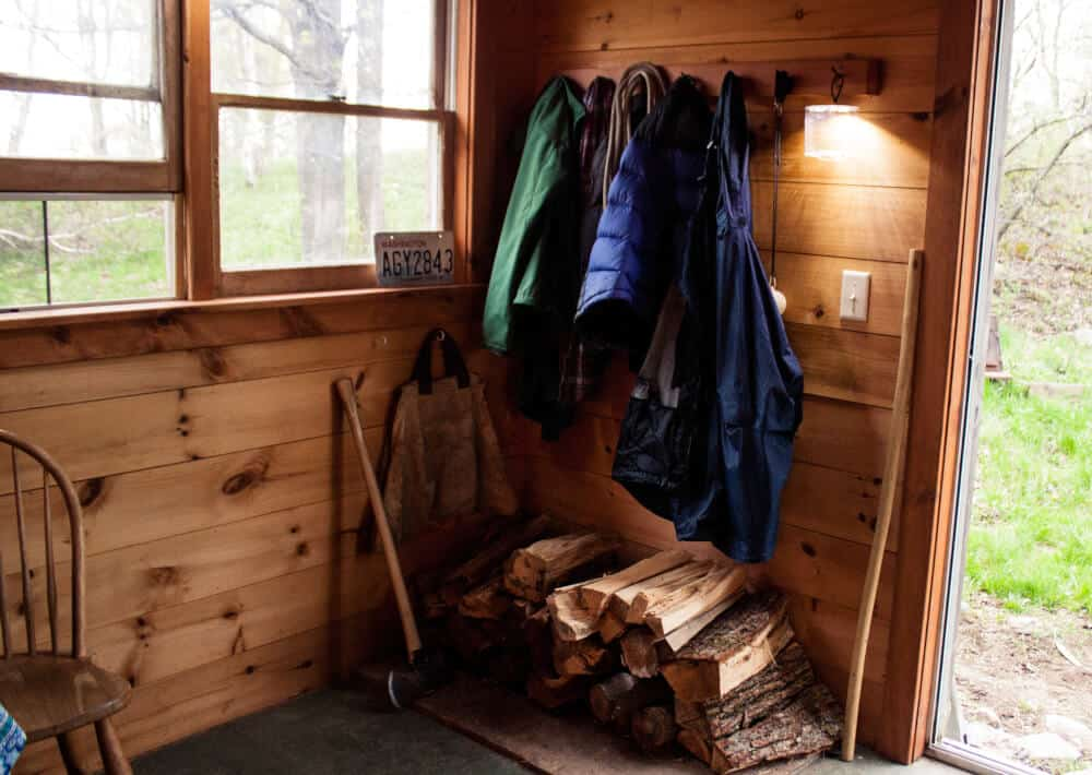 An interior shot of mountain cabin, Stony Pond Farm, Vermont. Firewood stacked in a corner below a coat hook with coats hanging.