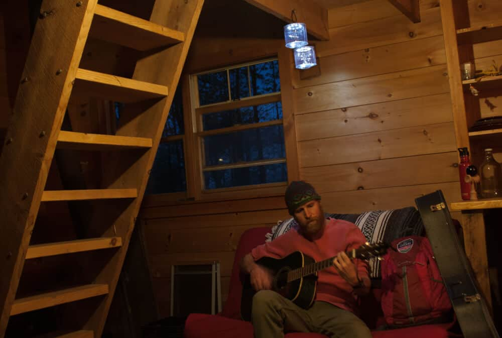 Eric playing the guitar under the loft stairs at the cabin rental on Stony Pond Farm