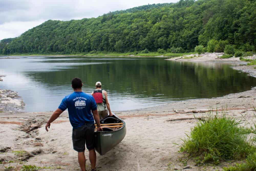 Two men carry a canoe down to the Connecticut River