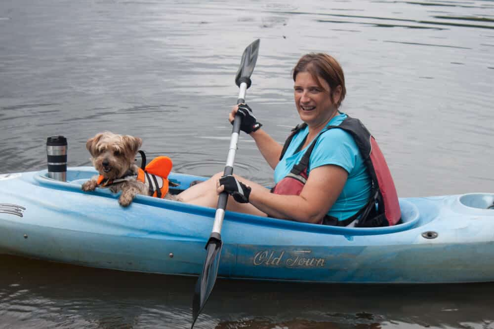 A woman paddles a blue kayak with a little dog