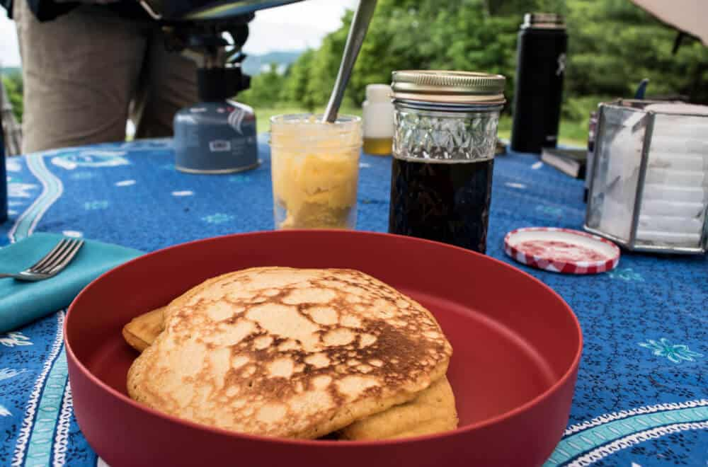 a red plate with pancakes on it. In the background is butter, syrup, silverware and a candle.