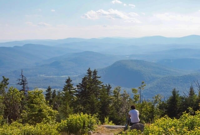 a hiker takes in the view on the summit of Mt. Ascutney in Vermont