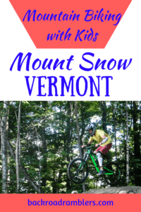 A young boy rides a mountain bike over a jump. Caption reads Mountain biking with kids at Mount Snow Vermont