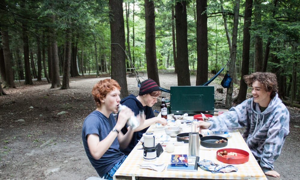 Three teenagers eat camp food at Emerald Lake State Park in Vermont