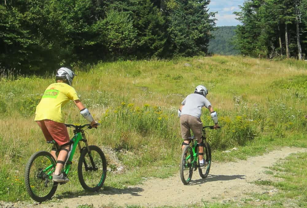 Two boys ride the mountain biking trails at Mount Snow in Vermont.