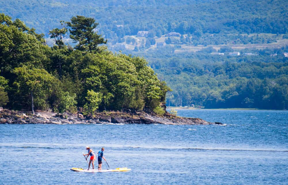 Two people paddle board of the shore of Burton Island State Park in the Lake Champlain Islands.