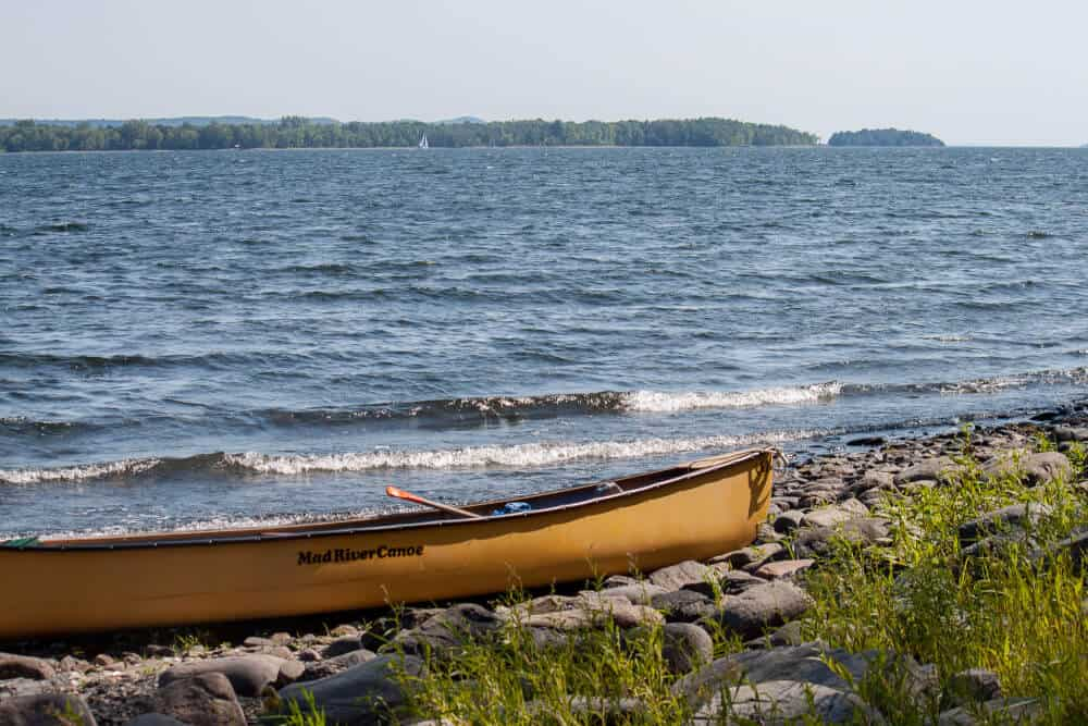 A yellow canoe rests on the shore of Woods Island in Lake Champlain, Vermont.