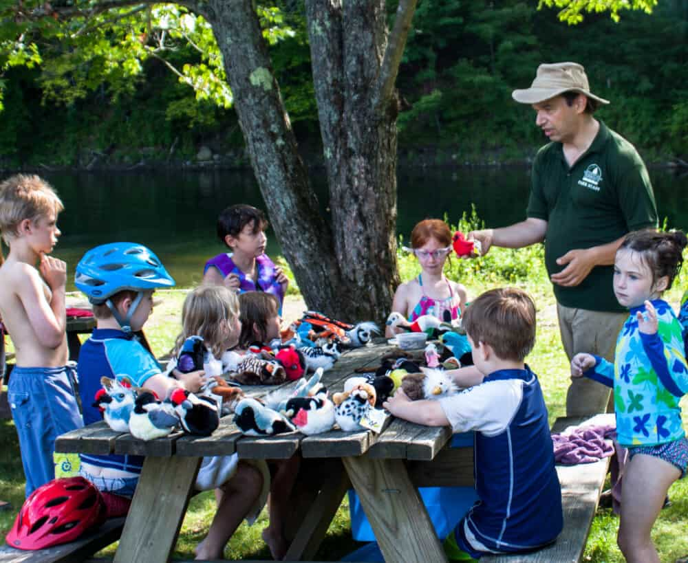 A park ranger talks to some kids about bird migration in Vermont at Little River State Park.