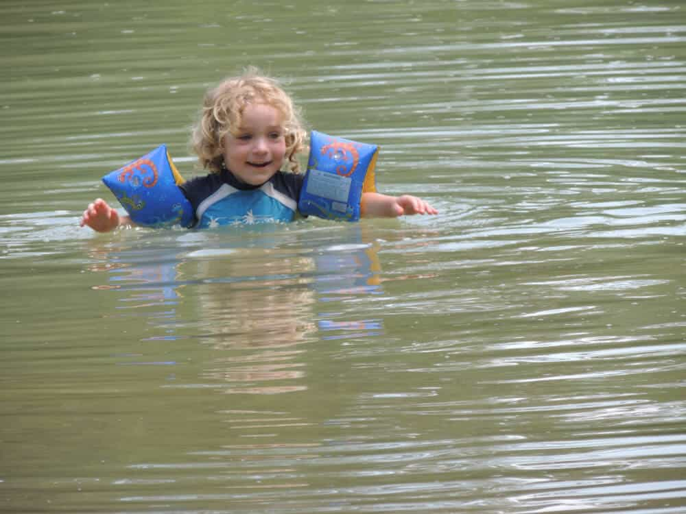 A small child enjoys swimming at Little River State Park