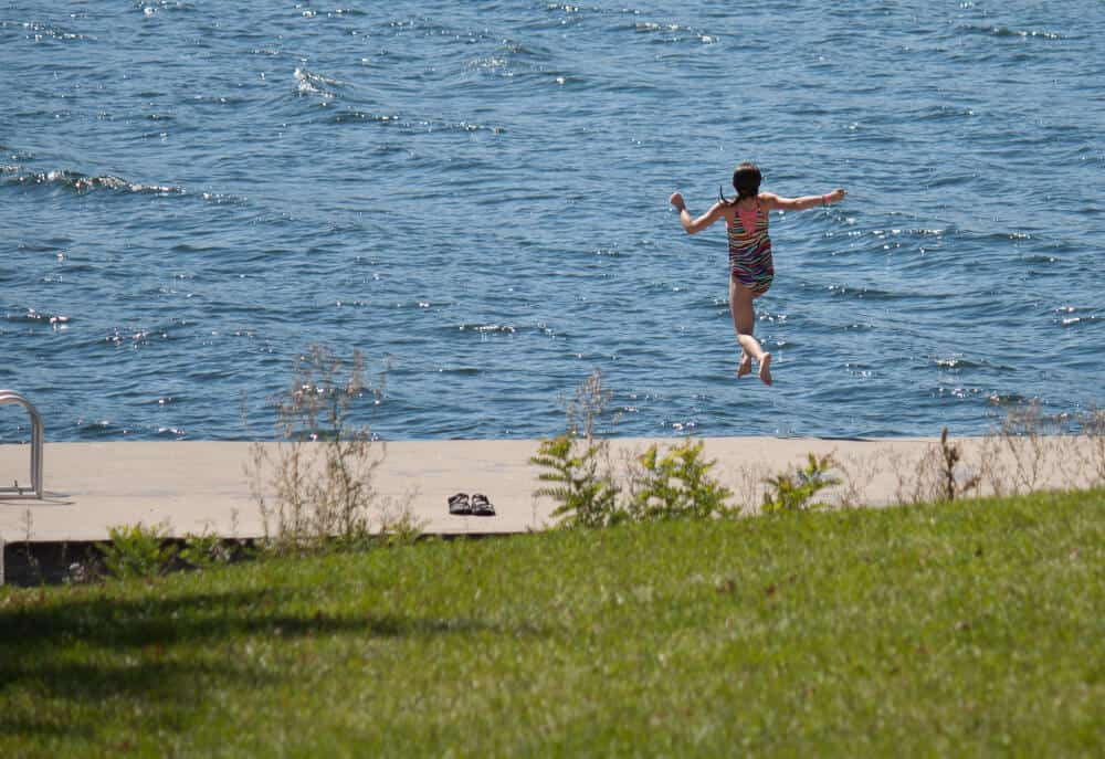 A young girl jumps into the lake in Kingsland Bay State Park in Vermont