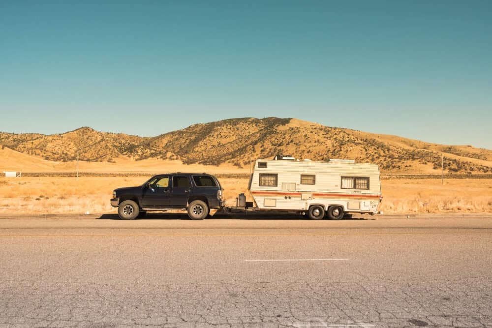 An SUV pulling an older camper through the desert.